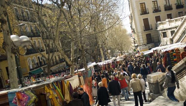 La gente va y viene entre los puestos de El Rastro, uno de los sitios favoritos de los madrileños.