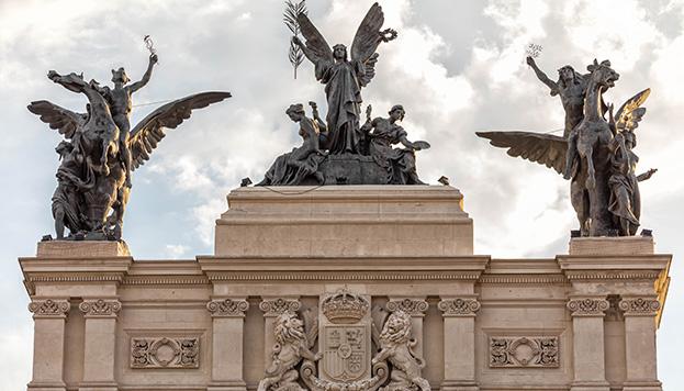 Y, justo, enfrente, la Gloria y dos Pegasos rematan el antiguo Palacio de Fomento.